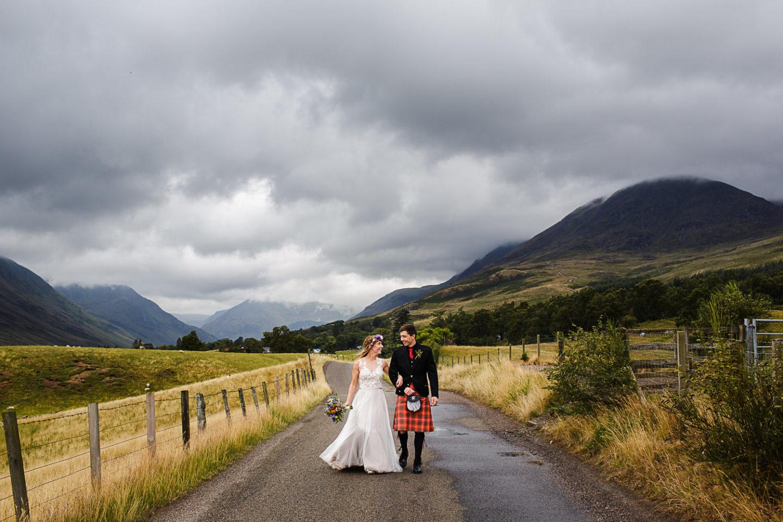 Newly married wedding couple walk in the landscape of Glen Clova in Scotland