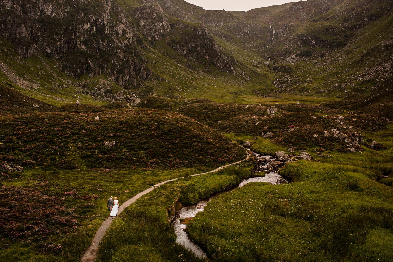 Wedding landscape of newlywed couple walking through The Cairngorm mountain range in Scotland near Glen Clova Hotel